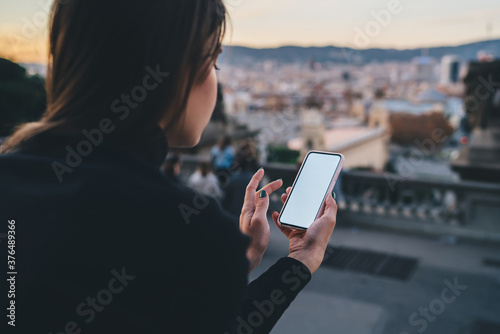 Fotografie, Obraz Unrecognizable woman browsing smartphone at city viewpoint