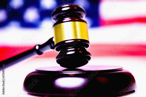 Photo Judge gavel against United States national flag as symbol of judicial system of the USA