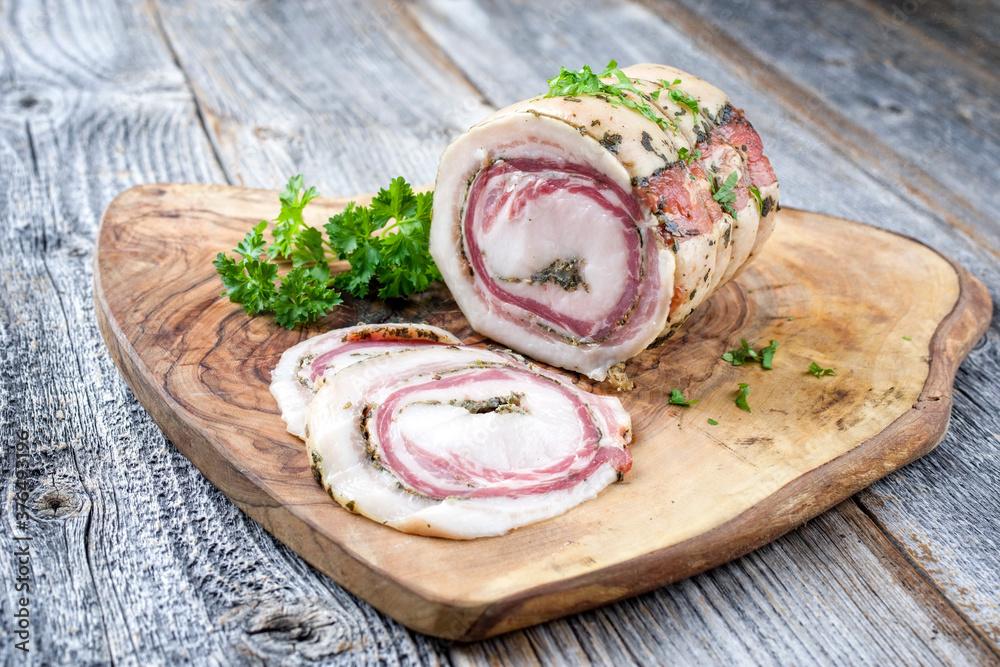 Traditionelle italienische Panchetta Arrotolata mit Schweinebauch angeboten als close-up auf einem rustikalen Holz Board mit Textfreiraum