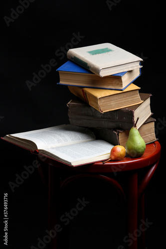 Fotografia Stack of books and apple and pear on dark black background