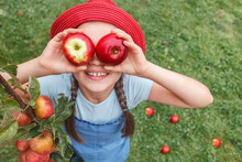 Little Girl In A Red Hat Holds Two Apples Near The Eyes On A Background Of Grass