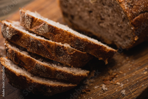 Fotografia close up view of fresh baked bread slices on wooden cutting board