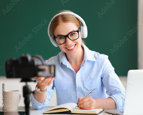 Fototapeta Delighted teacher recording online lesson.