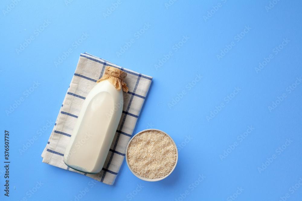 Fototapeta Rice vegan milk in glass bottle on blue background