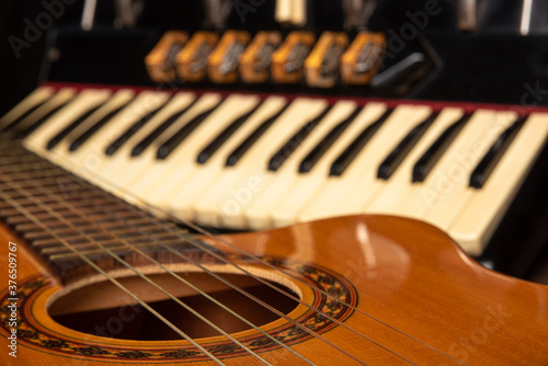 Fotografiet Old accordion and a beautiful guitar composing a scene on a rustic wooden surface with black background and low key lighting, selective focus