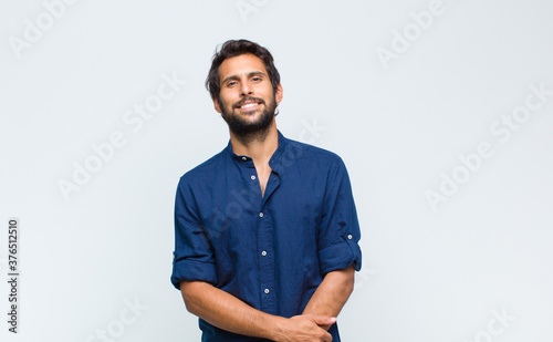 Obraz young latin handsome man looking happy, cheerful and confident, smiling proudly and looking to side with both hands on hips - fototapety do salonu