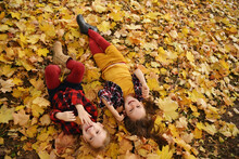 Portrait Of Two Cute Girls Friends Or Sisters Lying On The Leaves At The Autumn Park. Cute Kid Girl 4-5 Year Old Posing Outdoors, Has Happy Face, Long Hair. Walking In Park. Childhood.