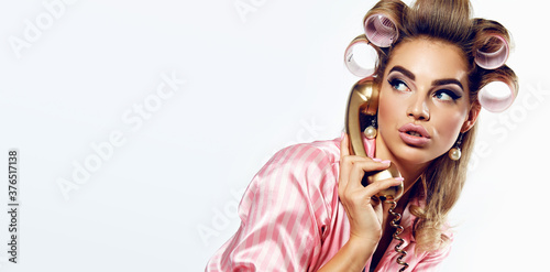 Papel de parede A beautiful young showy girl with bright pin-up make-up speaks on a golden dial telephone in pink striped silk pajamas and pink curlers