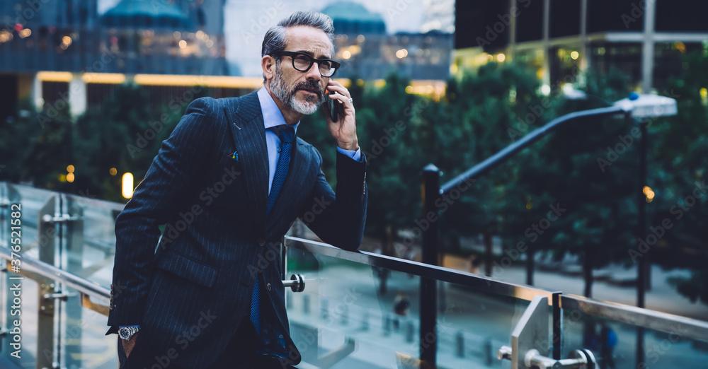 Fototapeta Adult businessman talking on phone against background of evening street
