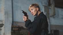 Young Woman Soldier In Black Uniform Aiming With A Pistol.