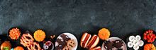 Halloween Party Food Bottom Border Over A Black Stone Banner Background With Copy Space. Top View. Spooky Mummy Pizzas, Finger Hot Dogs, Caramel Apples, Cupcakes, Donuts, Cookies And Candy.