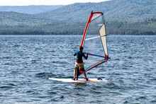 A Male Athlete Is Interested In Windsurfing. He Moves On A Sailboard On A Large Lake On A Summer Day
