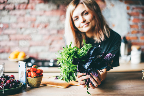 Obraz Woman holding greenery and looking to the camera with smile. - fototapety do salonu