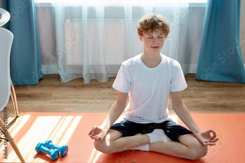 Fototapeta young caucasian teen boy exercising sport at home, practice yoga, sit in pose, keep calm, meditating obraz