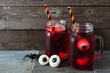 Creepy Halloween eyeball fruit punch in mason jars against an old wood background