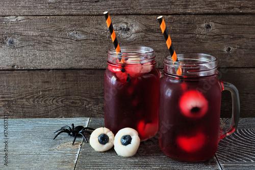 Obraz Creepy Halloween eyeball fruit punch in mason jars against an old wood background - fototapety do salonu