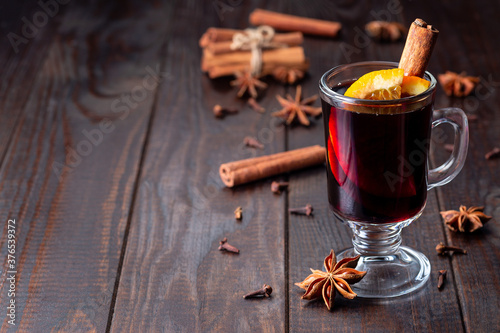 Obraz na plátně Red glogg or mulled wine with orange slices and cinnamon stick on dark wooden ba