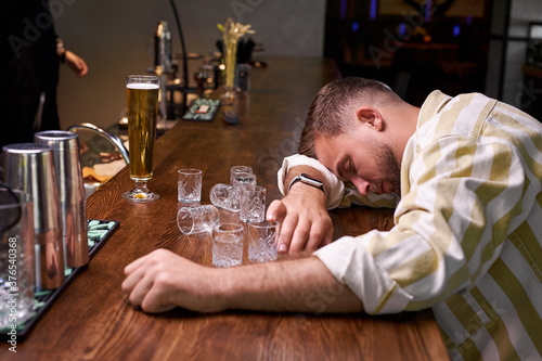 Fotografering very drunk man sleep in the bar , sits alone with empty glasses of alcohol