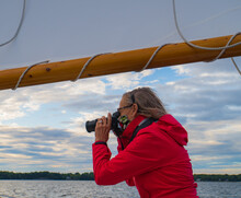 Senior Woman Photographer Taking Photographs From A Historic  Sailboat