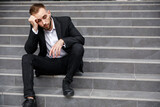 Fototapeta Na drzwi - businessman in formal clothes sitting on the street stairs worri