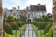 An Old Flag Stone Path Leads Up To An English Country House Viewed Through A Wrought Iron Gate. The Path Is Bordered By Elegant Topiary Bushes.