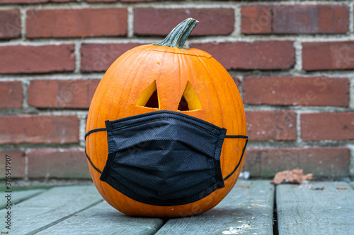 Carved pumpkin for Halloween wearing a Covid 19 face mask on a porch with a bric Canvas Print