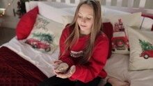 A Beautiful Long-haired Teenage Girl In A Red Hoodie Sits On A Bed With Christmas Decor And Holds A Live Mouse In Her Hands. Slow Motion