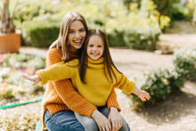 Stylish Woman With Dark Hair Holding Daughter On Her Knees. Outdoor Photo Of Glad Young Lady Having Fun In Autumn Park With Child.