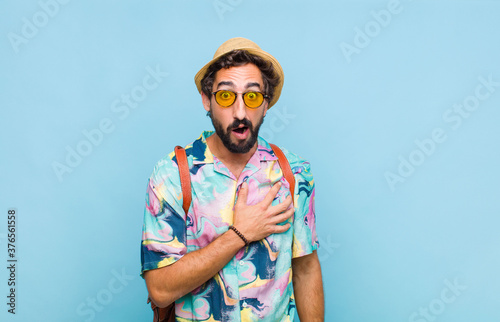Foto young bearded tourist man feeling shocked and surprised, smiling, taking hand to