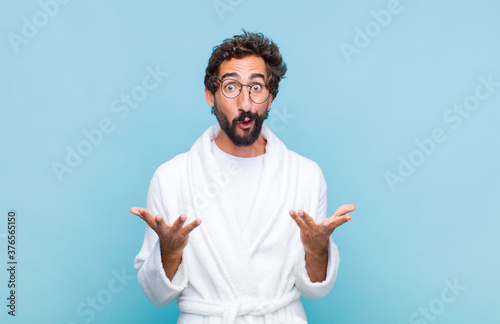 Foto young bearded man wearing a bath robe open-mouthed and amazed, shocked and aston