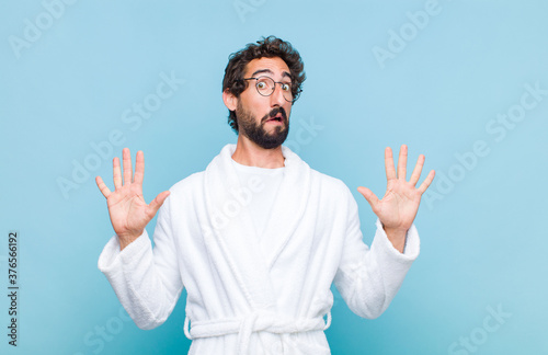 Photo young bearded man wearing a bath robe feeling stupefied and scared, fearing some