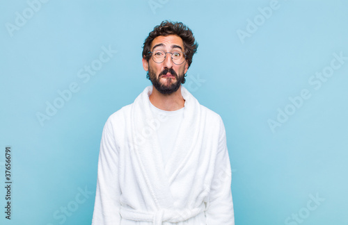 young bearded man wearing a bath robe feeling sad and stressed, upset because of Canvas