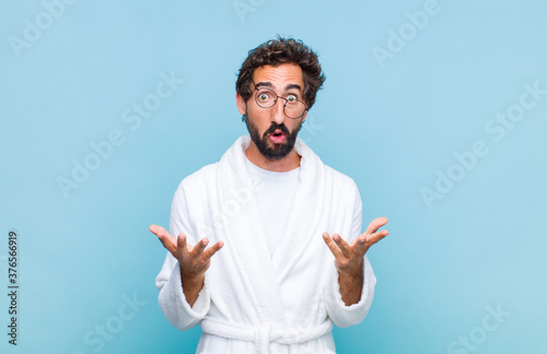 Fotografie, Obraz young bearded man wearing a bath robe feeling extremely shocked and surprised, a