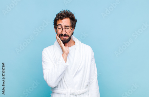Fotomural young bearded man wearing a bath robe holding cheek and suffering painful tootha