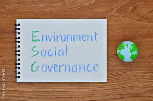 Photographie A sketchbook with Environment, Social, Governance written on it is placed diagonally on a wooden board