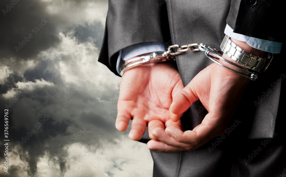 Fototapeta Male hands in handcuffs behind his back