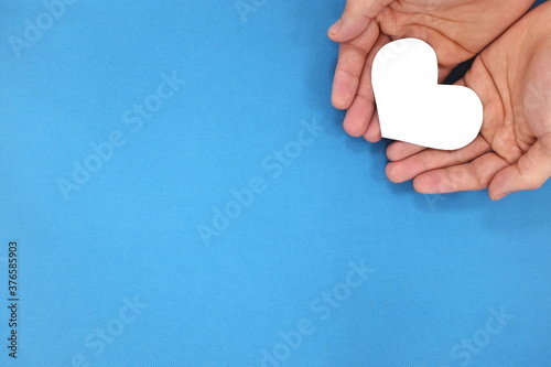 Photo Male hands holding a white heart in blue background top view