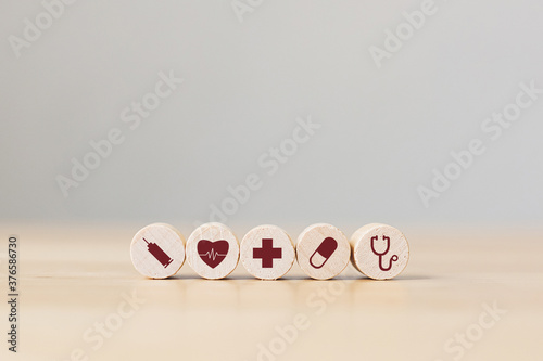 Fototapeta Conceptual of health care and insurance. Wooden sphere on wood table with icon healthcare obraz