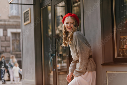 Charming European girl in warm cashmere sweater smiles sweetly into camera again Wallpaper Mural
