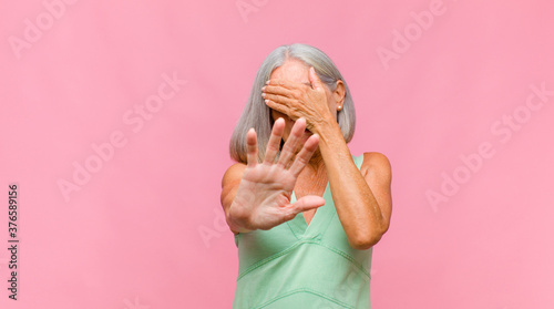 middle age pretty woman feeling disgusted, holding nose to avoid smelling a foul Fototapete