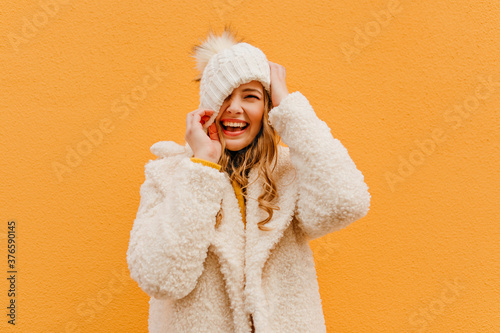 Obraz Portrait of girl having fun on isolated background in woolen coat. Blonde puts hat on face - fototapety do salonu