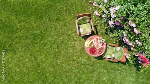 Obraz Decorated table with bread, strawberry and fruits in beautiful summer rose garden, aerial top view of romantic date table food setting for two from above  - fototapety do salonu