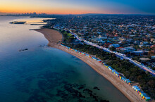 Aerial Sunset View Of Brighton Beach, With St Kilda Marina And The City Of Melbourne In The Distance, Captured At Dusk