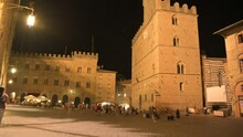 Volterra,Tuscany,Italy.August 2020. Night Footage In The Magical Atmosphere Of Piazza Dei Priori. Three-quarter View Of The Homonymous Building, The Wind Moves The Flags Slightly, People In The Square