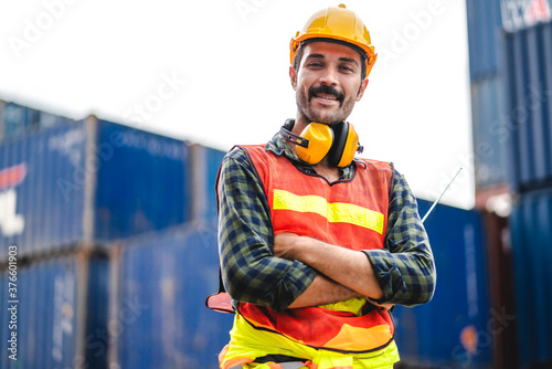 Professional engineer container cargo foreman in helmets working standing and using walkie talkie checking stock into container for loading Fototapet