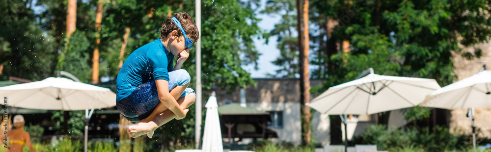 Fototapeta panoramic shot of kid in t-shirt and swim goggles jumping and plugging nose