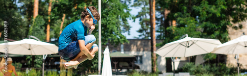 Fototapeta panoramic shot of kid in t-shirt and swim goggles jumping and plugging nose obraz