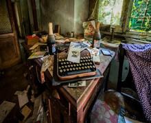 Typewriter And Photographs In Abandoned Old House With Dust And Cobwebs