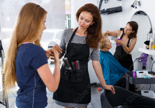 Professional hairdresser inspecting hair of teenage girl before haircutting in hair salon Wallpaper Mural