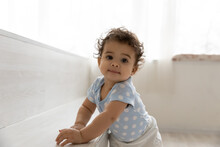 Portrait Of Adorable Little African American Baby Boy Or Girl Relying On Furniture, Learning Making First Steps Indoors. Happy Curious Cute Mixed Race Toddler Walking, Childcare Development Concept.